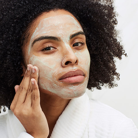 Woman applying Aveeno face mask